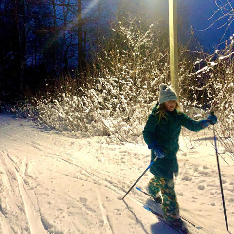 Young girl cross country skiing under the lights at Swedetown trails in Calumet