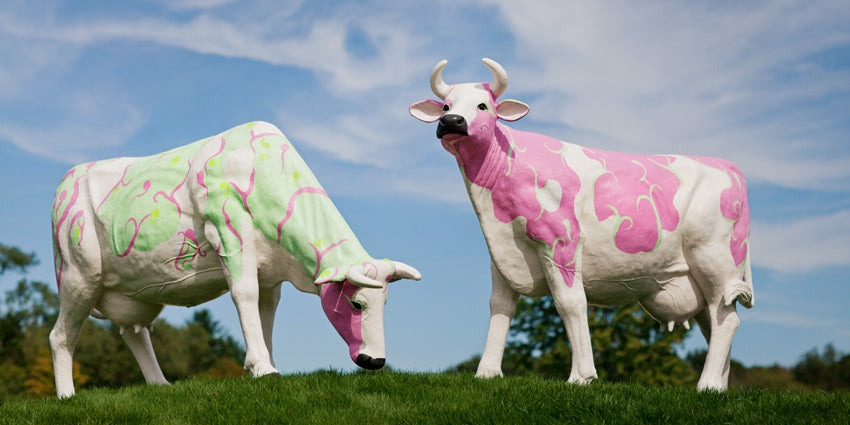 Two cows sculptures, painted in pastel colors as decorative objects of a landscape in a wedding