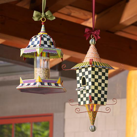 A colorful birdhouse, and a bright bird feeder, hanging from a gutter.