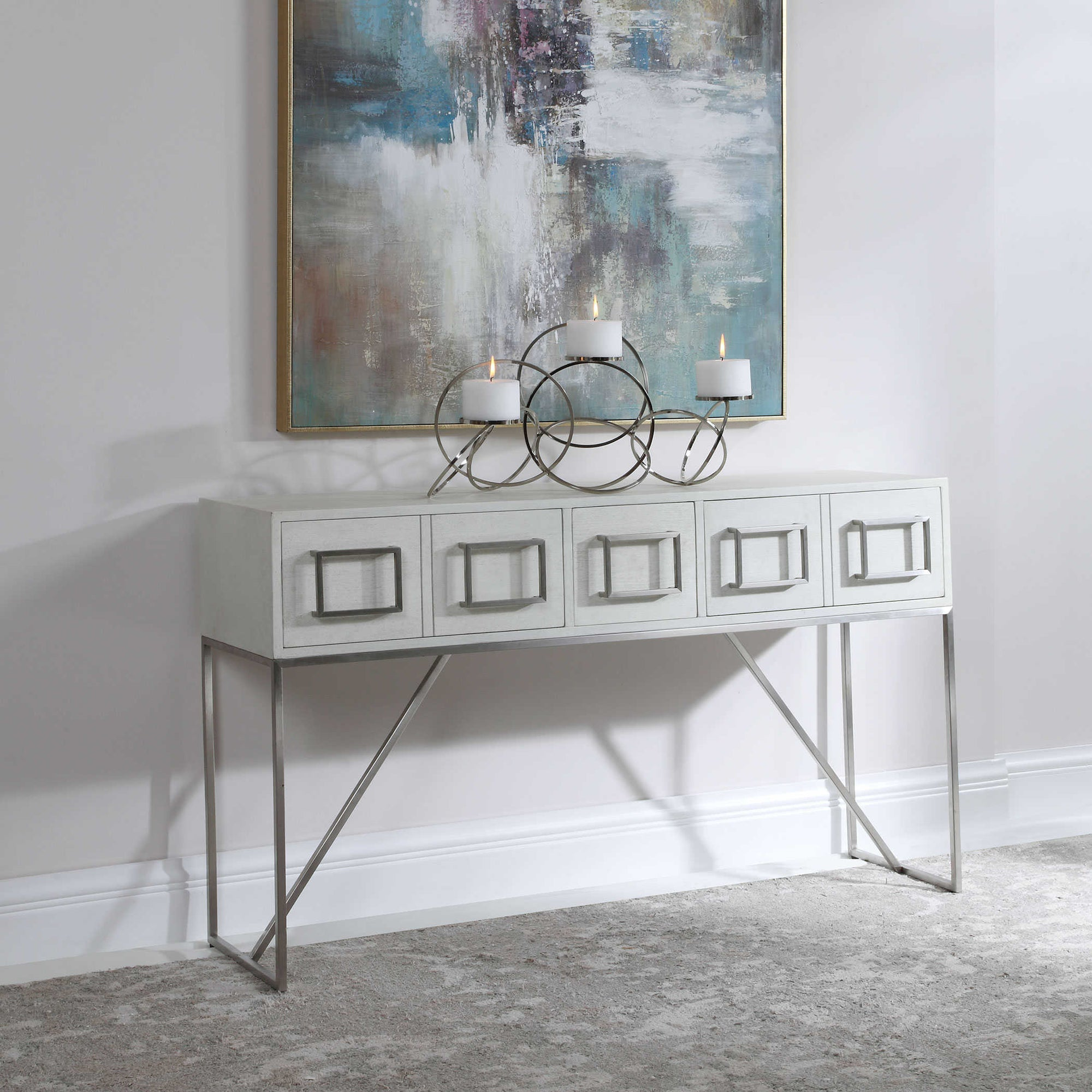 A white sideboard table, with doors and square silver handles, silver finish legs, and a set of candles on top of it.