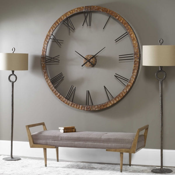 A large round wall clock, hanging on an olive green wall, a bench, and one lamp on each side of the bench to complete this modern space.