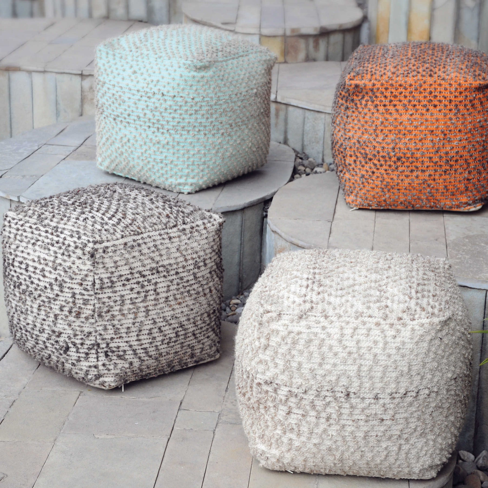 Four Handwoven Poufs with a neutral beige cotton, grey, orange and aqua marine.