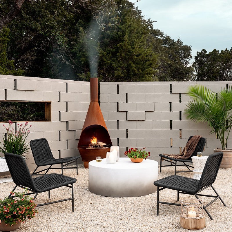 A Modern patio with Scandinavian style grey walls, an iron cast fireplace, four outdoor chairs, a round coffee table, and an end table, the floor is cover with some kind of stones, and there are some green plants around the patio.