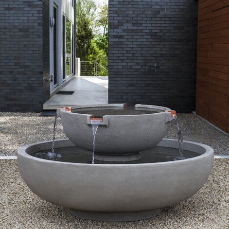 A cast stone round fountain with a modern and minimalistic style, placed over the gravel patio floor of a modern house, with a black bricks wall on the background.