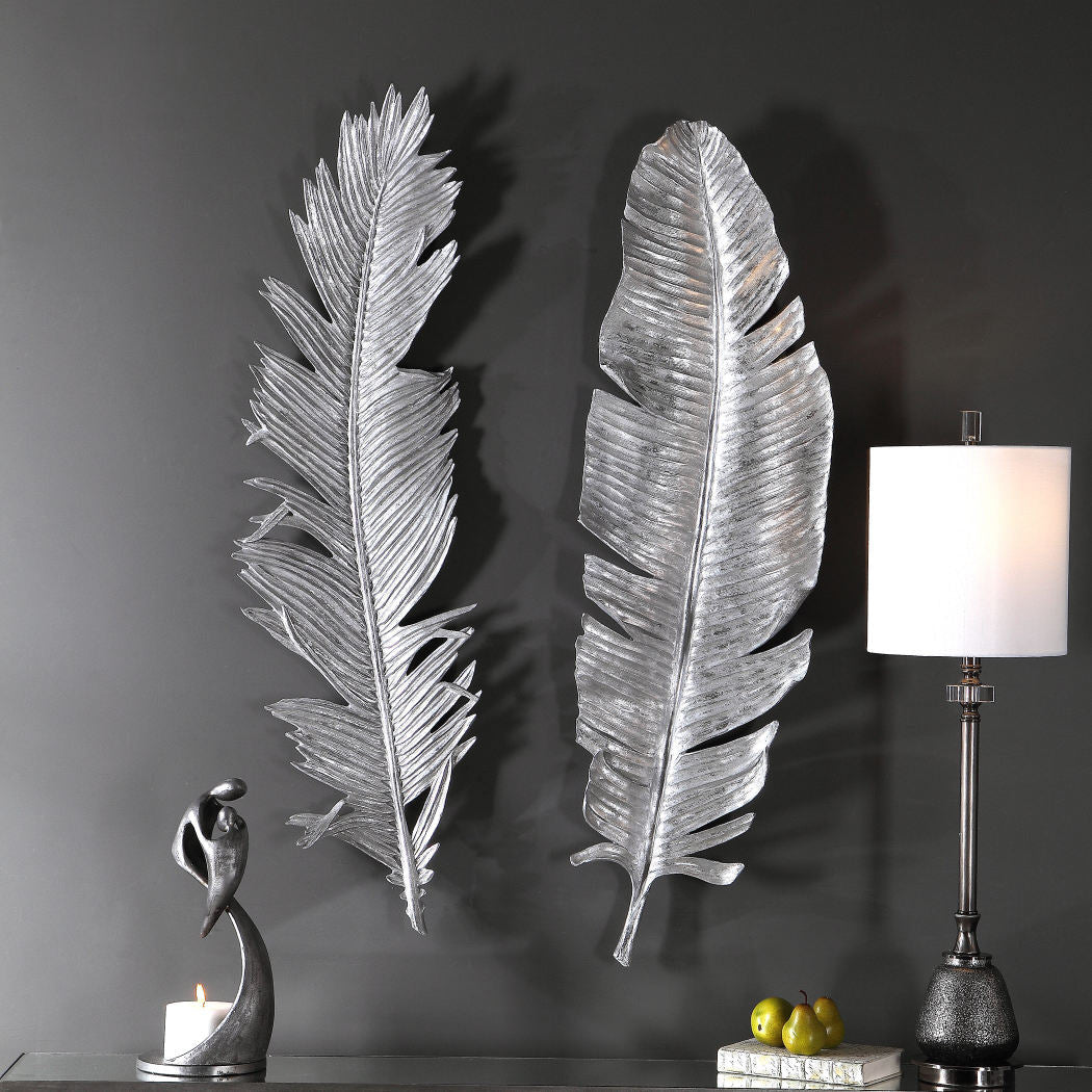 A grey wall featuring two beautiful and stylish metal leaves, these pieces of wall art are big and shiny, a small statue and a lamp on a table complete the gorgeous scene