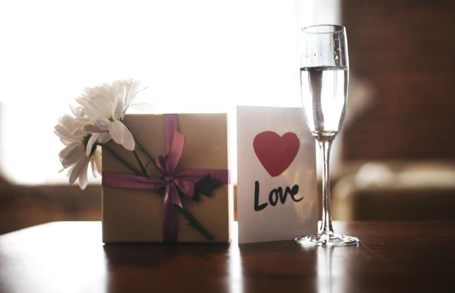 A small gift wrapped with flowers next to a champagne glass and a love envelope