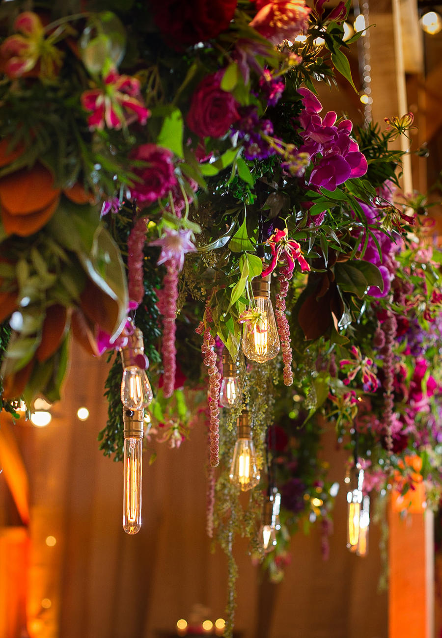 A gorgeous light fixture decoration with deep purple flowers and red roses, and vintage bulb lights for a wedding decoration