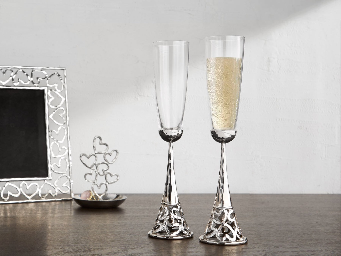 Two toasting flutes with a silver vase, designed with heart shape on the bottom, a picture frame with the same hearts shape and silver finish in the background, and a small sculpture with stacking little hearts.