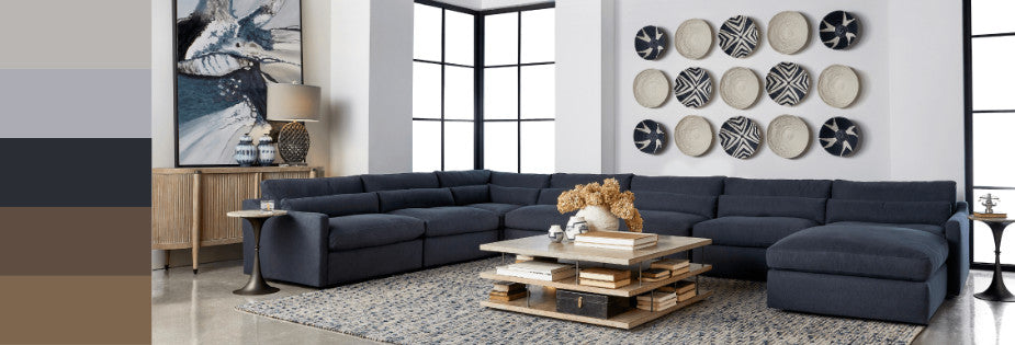 a modular large couch in a navy blue intense color, stunning artwork on the back wall, and a low brown coffee table