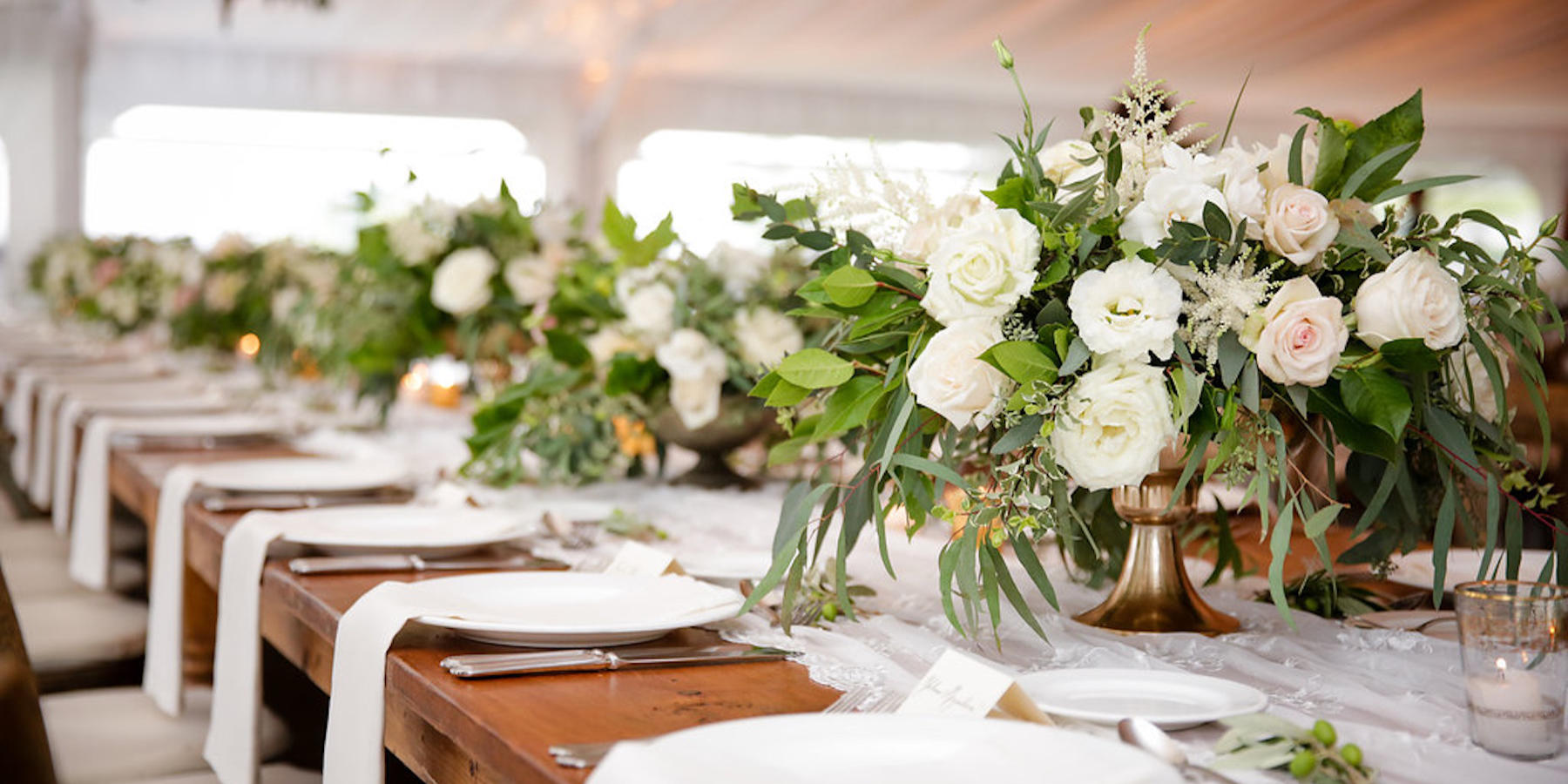 A wedding table, with gorgeous flowers arrangements on gold vases, and a neat table set up