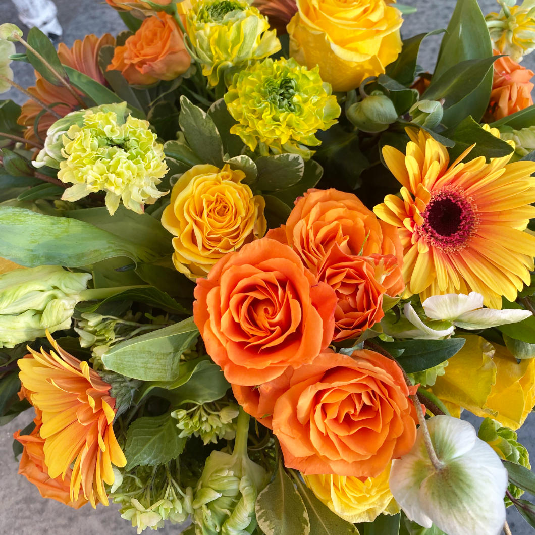 A beautiful citrus toned flower arrangement. A mix of lemon, limes, bright oranges, and stunning yellows. The arrangement features green Hellebore, green and white Parrot Tulips, orange crush Spray Roses, Kiwi Hydrangea, and large two-toned Gerbera Daisys. In a clear glass cylinder. next to it, a plate with lemons and limes, an