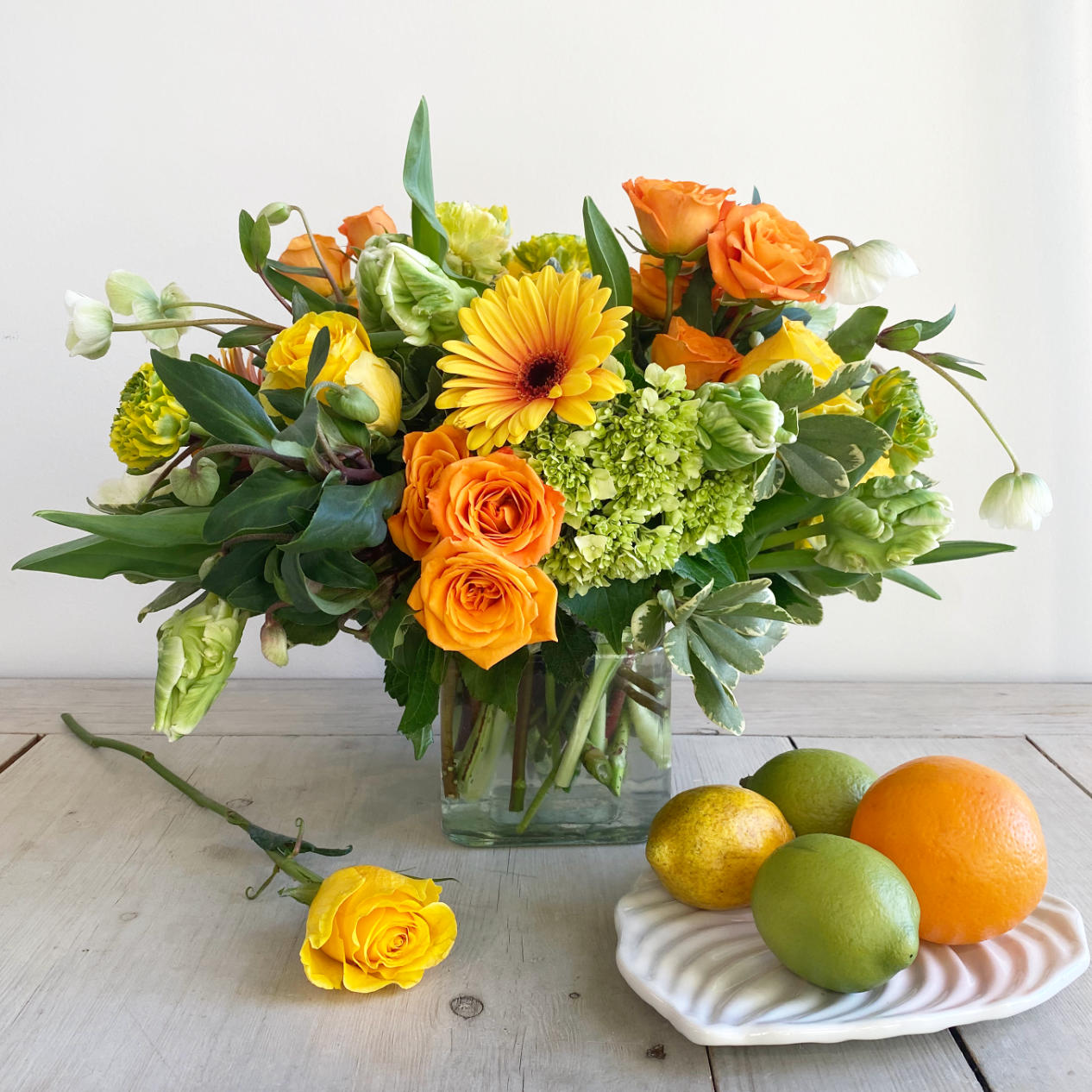 A beautiful citrus toned flower arrangement. A mix of lemon, limes, bright oranges, and stunning yellows. The arrangement features green Hellebore, green and white Parrot Tulips, orange crush Spray Roses, Kiwi Hydrangea, and large two-toned Gerbera Daisys. In a clear glass cylinder. next to it, a plate with lemons and limes, and there is a yellow rose over the table