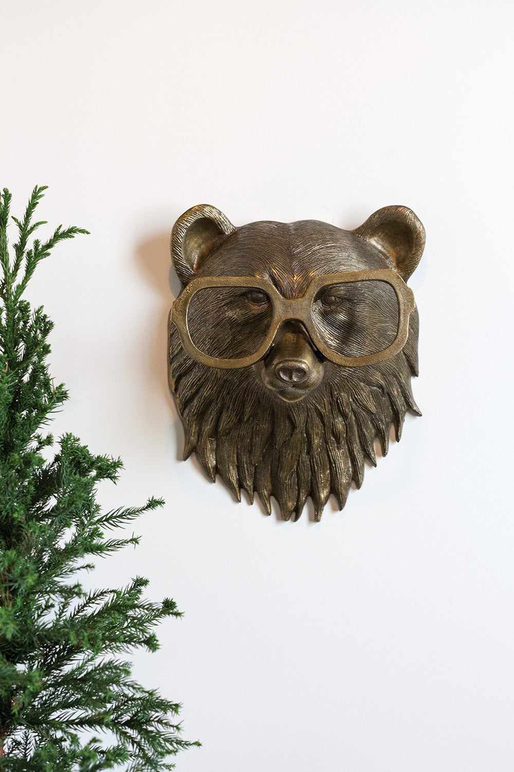 a head of a bear in metal with brass finish. the bear is using big readers
