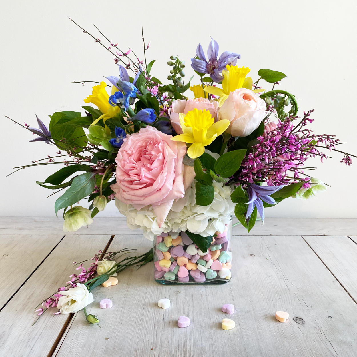 A cube arrangement featuring a mix of spring blooms. Pink O'Hara Garden Roses, Juliet Roses, Daffs, Hellebore, Clematis, and Heather Flowers. With edible conversation hearts.