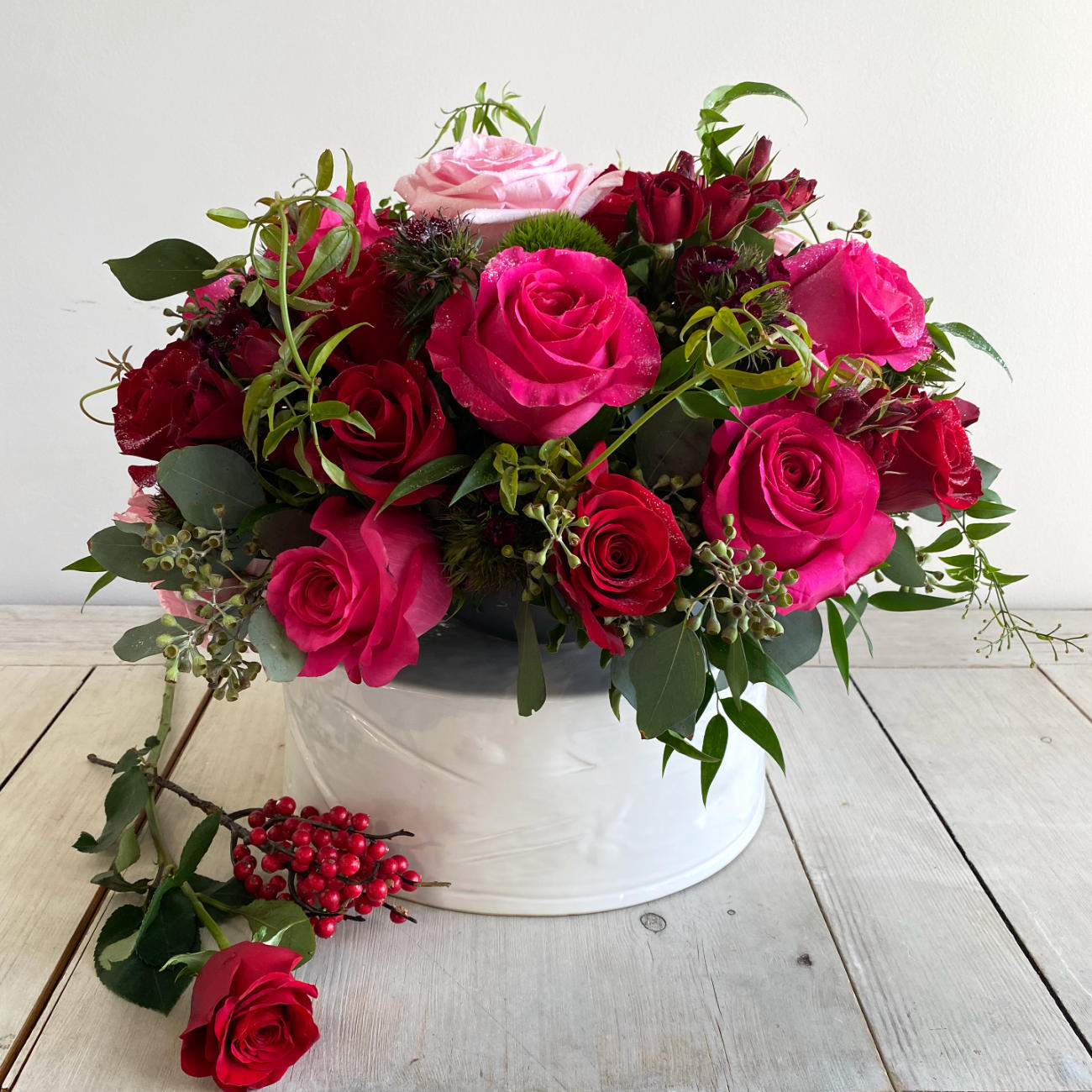 A Jaw-dropping floral design that showcases the pure beauty of a rose. A stunning arrangement of paved mixed roses and greens. Featuring red hearts roses. Pink Floyd Roses and romantic O'Hara garden roses. Topped with a touch of glitter.