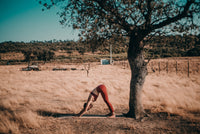 Yogi doing the downward facing dog yoga pose under a cork oak tree. She uses the Alba Yoga cork yoga mat to do her yoga practice. Picture was taken in the south of Portugal in the region called Alentejo. It stands for made in Portugal by Alba Yoga.