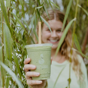 Girl holding a green smoothie through palm trees highlighting the reed straw