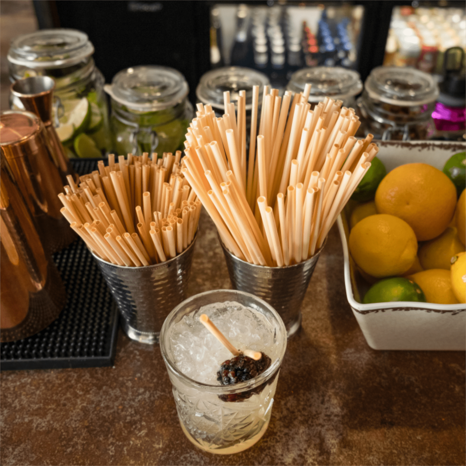 Holy City Straw Company Tall and Cocktail Straws in a straw holder at Bar with Drink