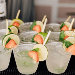 Multiple-Cocktail-drinks-with-strawberries-limes-and-a-wheat-stem-straw