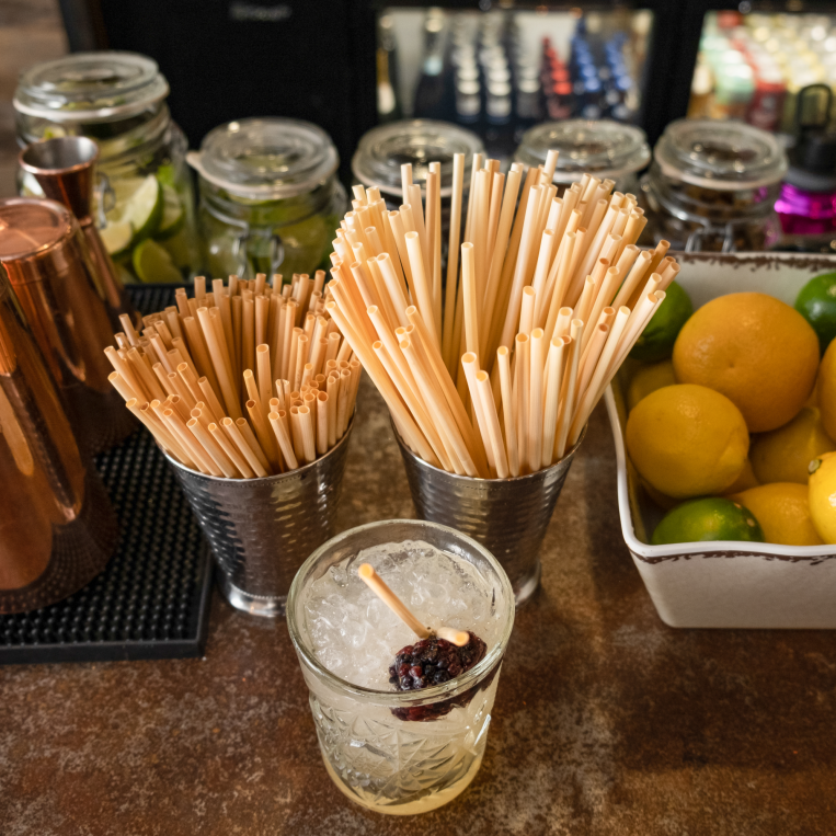 Holy City Straw Company Tall and Cocktail Straws in a straw holder at Bar with Drink alongside other bar top accessories