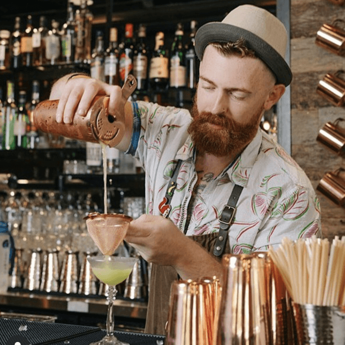Guy mixing drinks at a bar with wheat straws sitting next to him