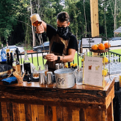 bartender-with-mask-on-pouring-a-drink-in-front-of-a-mobile-bar