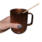 Hand holding an Ember coffee mug with a wheat stem straw inside