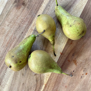 4 conference pears on a wooden board
