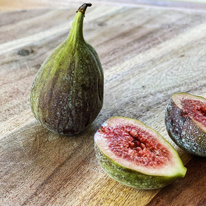 fresh figs, one cut open on a wooden board