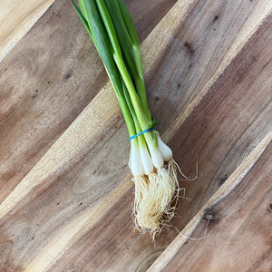 bunch of fresh green spring onions on a wooden board