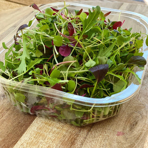micro salad leaves in a punnet on a wooden board
