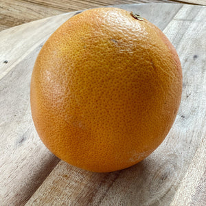 whole yellow grapefruit on a wooden board