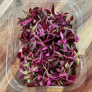 red amaranth leaves in a punnet on a wooden board