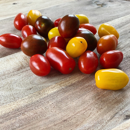 collection of Heirloom cherry tomatoes on a wooden board
