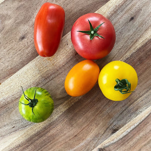 collection of Heirloom tomatoes on a wooden board