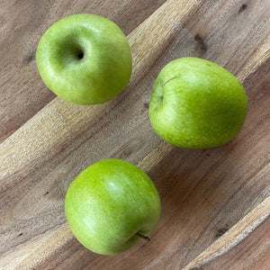 crisp fresh green granny smith apples on a wooden board