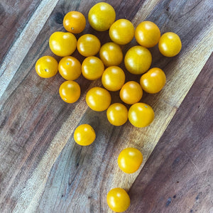 Loose yellow cherry tomatoes on a board