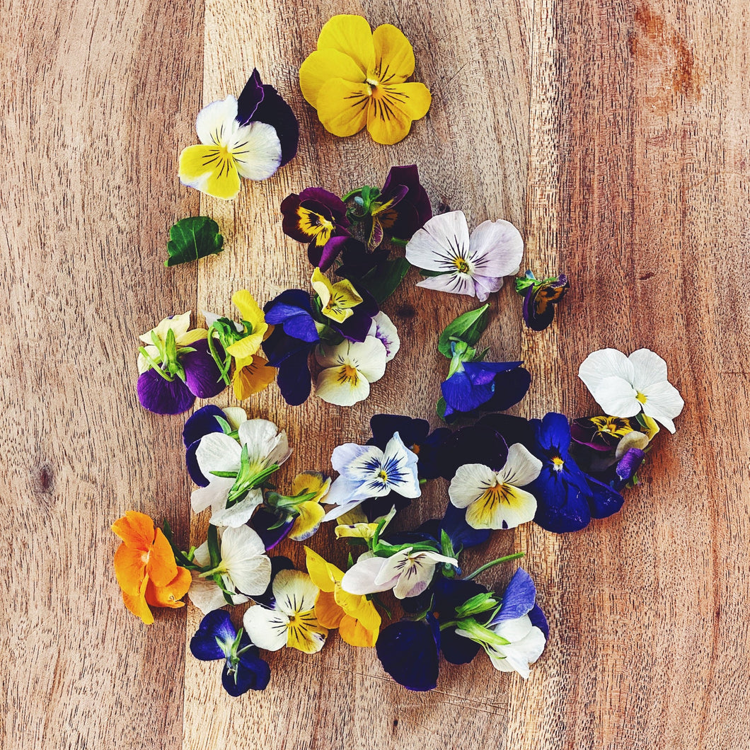 edible viola flowers on a wooden board