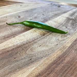 fresh green chilli on a wooden board