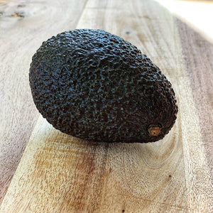 ripe hass avocado on a wooden board