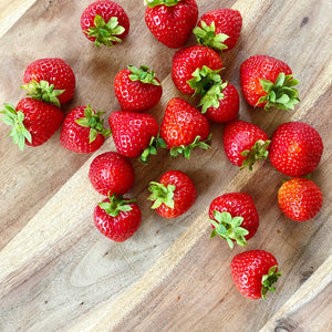 collection of fresh british strawberries on a wooden board