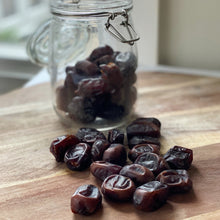 Load image into Gallery viewer, persian dates in a glass jar and loose on a wooden board