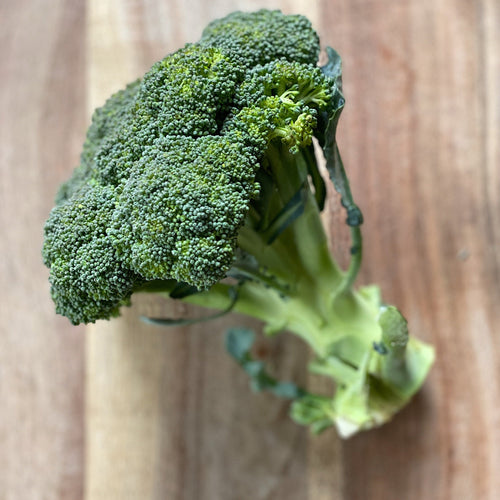 crown of brocolli on a wooden board