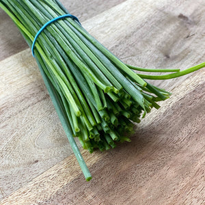 bunch of fresh chives on a wooden board