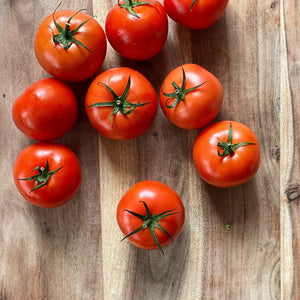 9 fresh red tomatoes on a wooden board