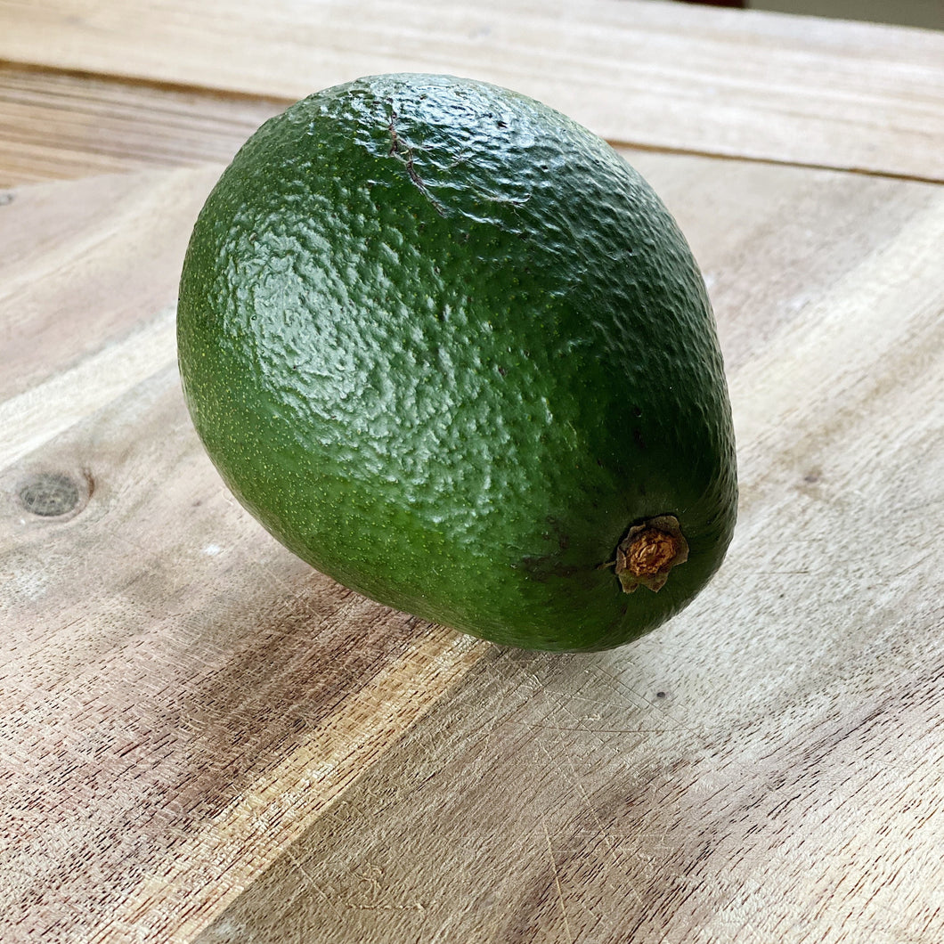 green avocado on a wooden board