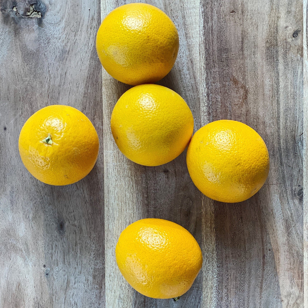 5 small fresh oranges on a wooden board