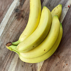 bunch of 5 bananas on a wooden board