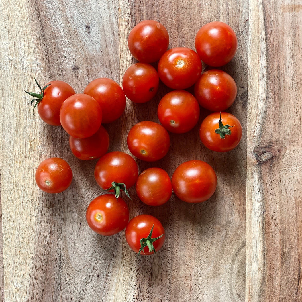 fresh cherry tomatoes on a wooden board