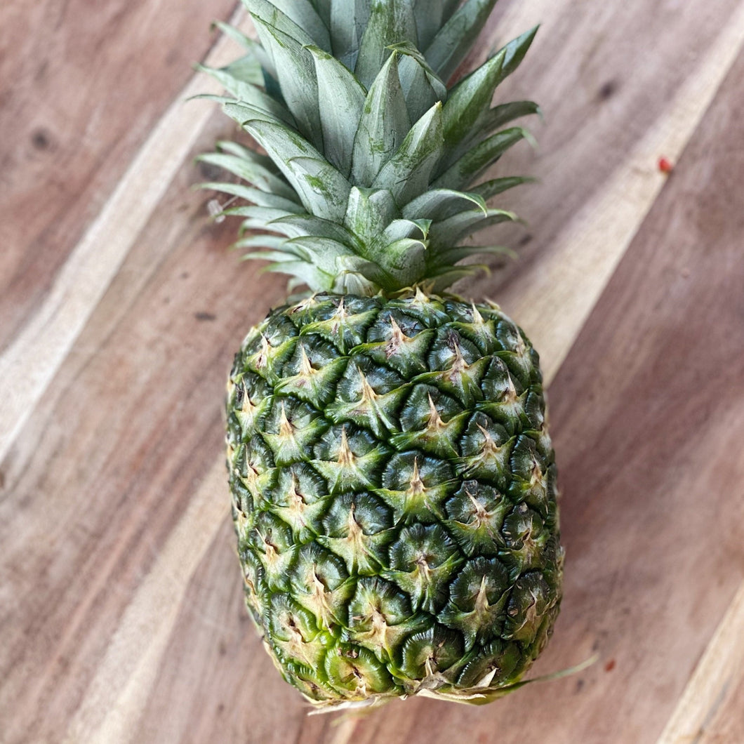 whole pineapple on a wooden board